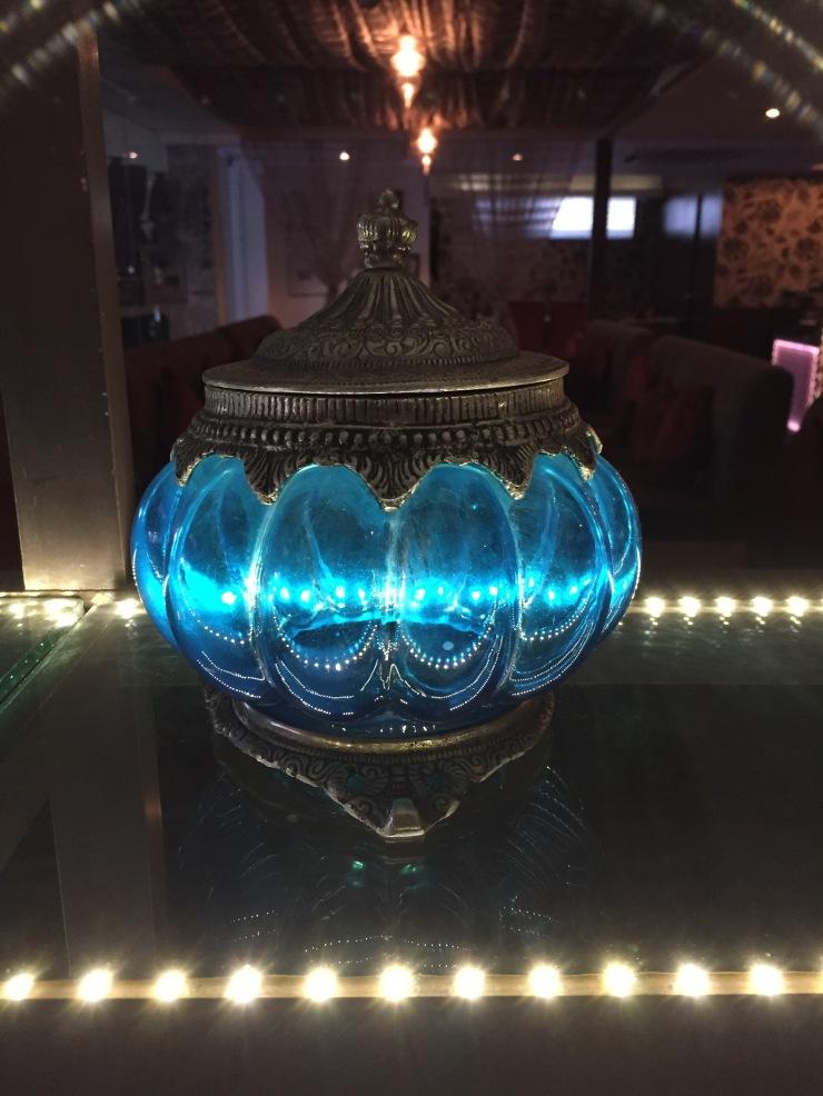 The blue glass pot kept on a glass shelf